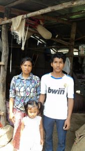 Kosal, his mother and sister in front of their house Cambodia