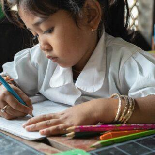 Cambodian girl in school writing