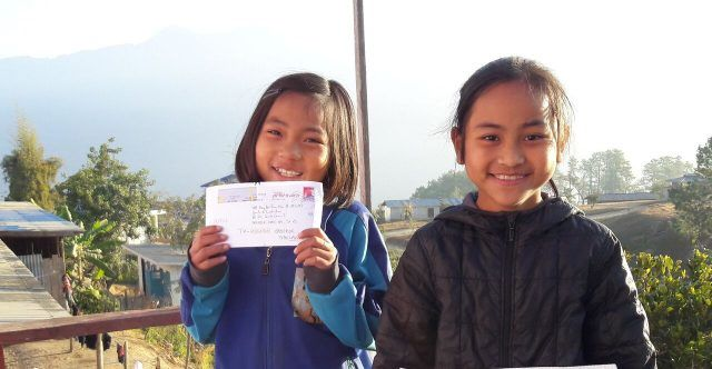 child holding the letter she received from her sponsor