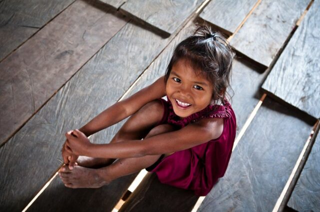 Smiling Cambodian girl in her wooden house