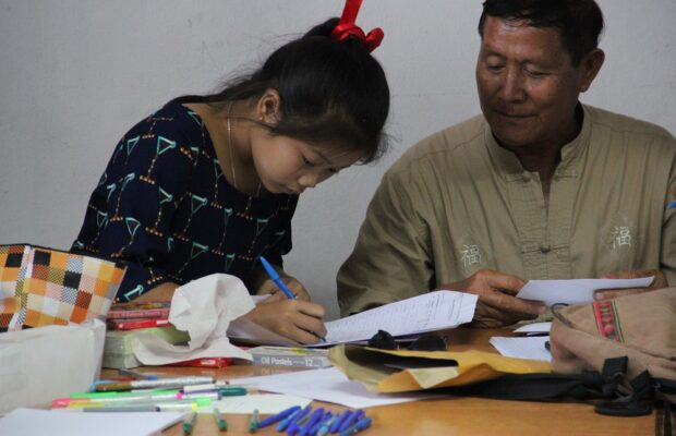 Linthy helping a young girl doing her homeworks