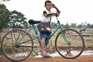 boy going to school in his cycle Cambodia