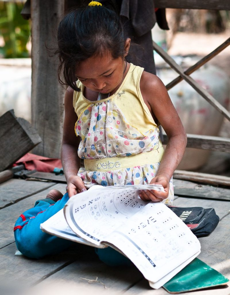 little girl studyig at home in rural cambodia
