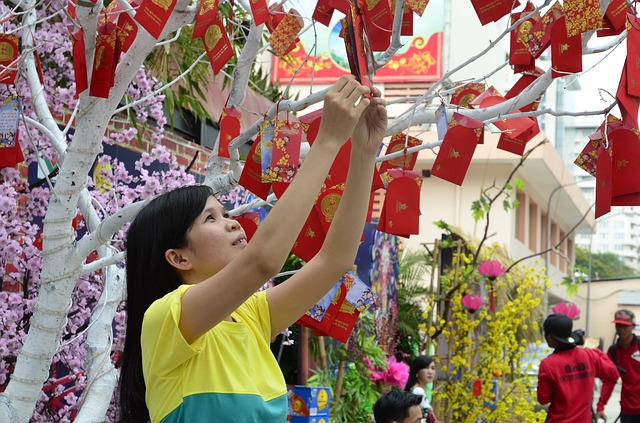 A young Vietnamese girl hanging up a red envelope (Image: Bruce Lam, Pixabay)