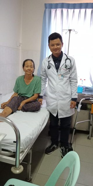 Reasey standing next to a patient looking at the camera