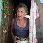 Inayawan elderly woman receiving food looking at the camera