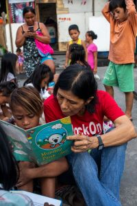 Mam'Percy reading with a child in a Manila shantytown