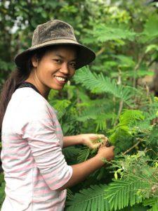 Sreymao smiling at the camera next to a tree