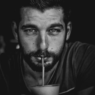 Tom Photographer and traveller, black and whote photo, looking into the camera and sipping a drink