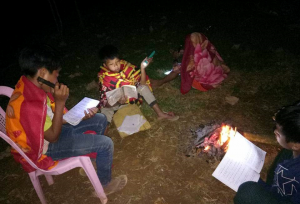 young people studying by flash light after dark in Kachin state