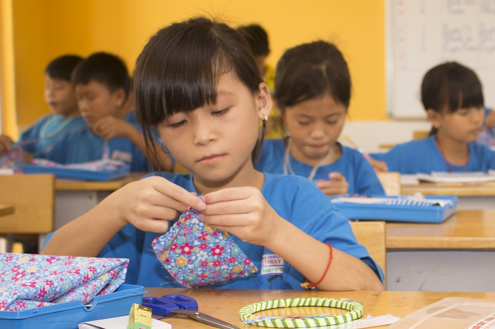 Vietnamese child sewing at the Maison Chance school