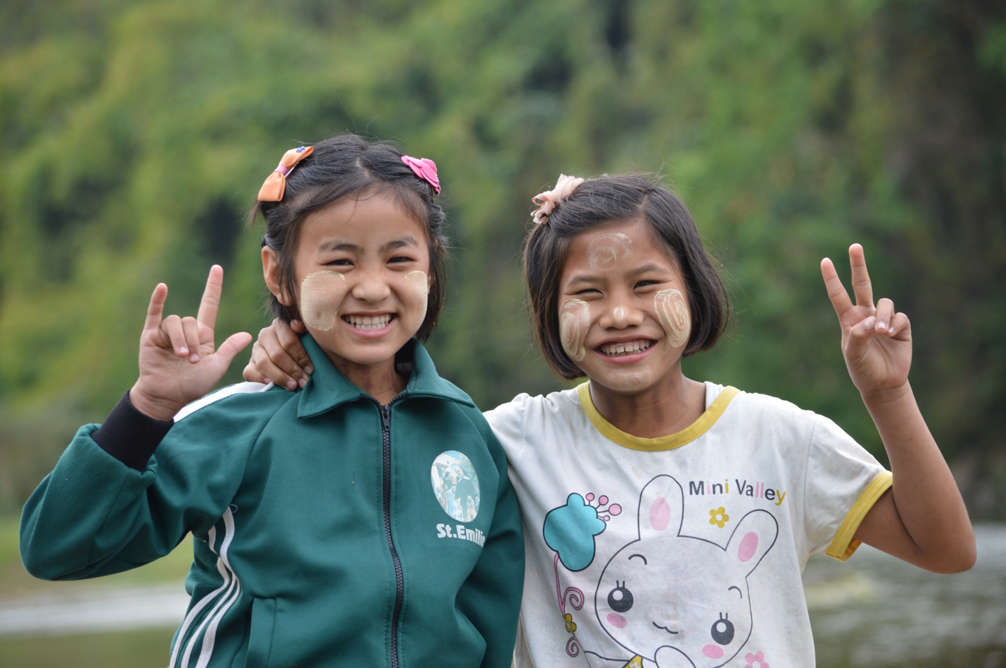 Two young girls smiling and looking at the camera