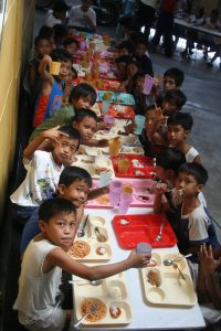numerous Filipino children eating looking at the camera