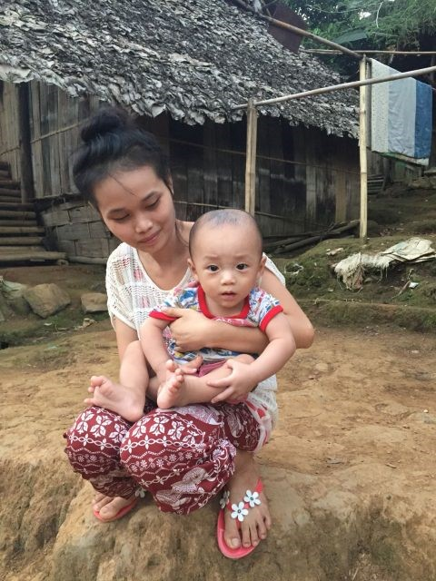 A mother and son watching a football game. Distractions are rare in camp Mae La Oon, baby, refugee, Burma, Myanmar, Child